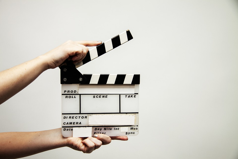 Hands holding a clapperboard.